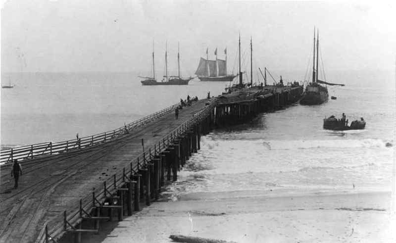 "Hueneme Wharf with view of schooners at anchor and the steamer ""Yaquina"" beached and wrecked"
