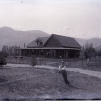 Man with rifle(?) in front of house