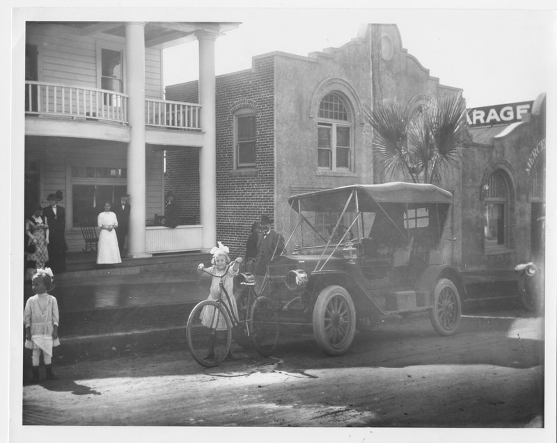 Mercer's Garage with girl and car in front