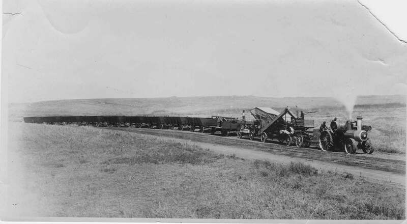 Wagons full of lima beans and a threshing machine been pulled by steam tractor