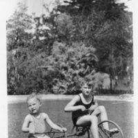 Two children riding tricycles