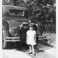 Girl posing behind an automobile