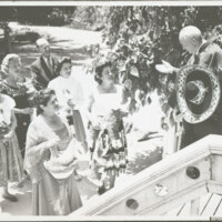 A Man in Spanish Costume Talks to a Group of Women